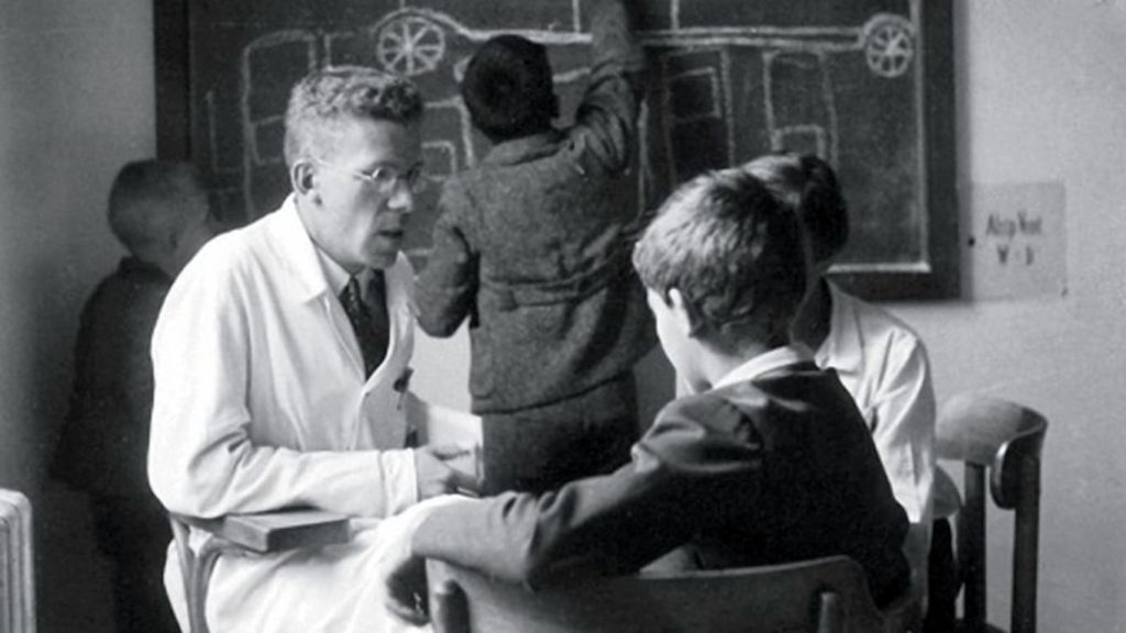 A slim male in a lab coat and glasses working with children in a clinic)