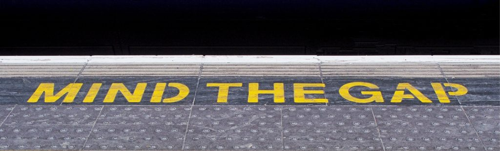 An image of a train platform with the words 'Mind the gap' on bold, yellow capital letters