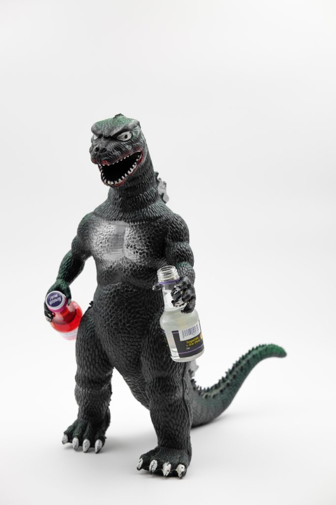 Godzilla (a giant dragon/lizard film character) hold a bottle of clear liquid and a bottle of red liquid